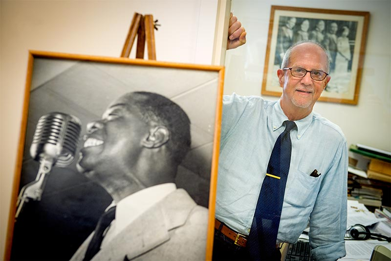 Bruce Raeburn poses with a portrait of Louis Armstrong